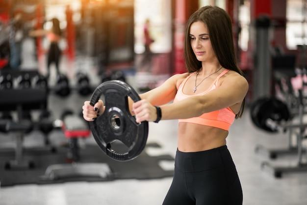 Frau an der turnhalle trainierend mit gewichtsplatte