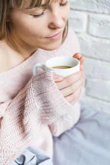 Frau an einem kühlen morgen mit einer heißen kaffeetasse warm
