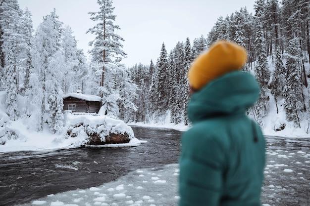 Frau an einem zugefrorenen fluss in lappland, finnland