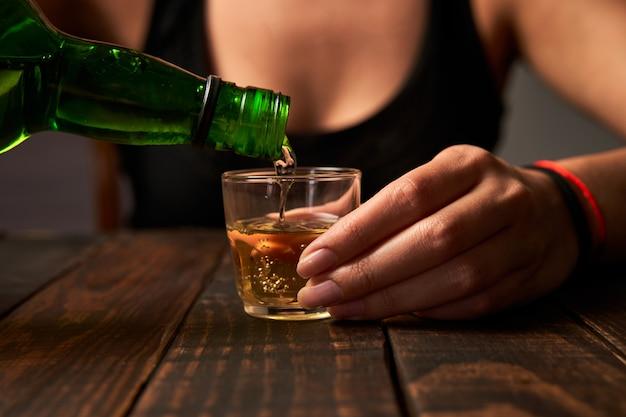 Frau an einer bar, die alkohol in ein schnapsglas gießt.