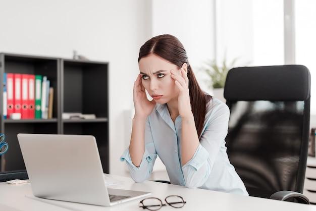 Frau an ihrem arbeitsplatz, der mit laptop im büro arbeitet