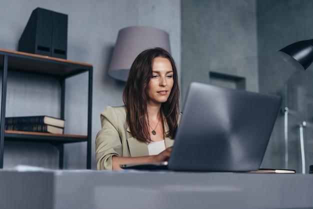 Frau an ihrem schreibtisch mit einem laptop, der von ihrem büro arbeitet.
