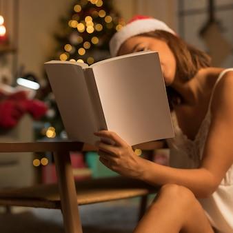 Frau an weihnachten, die ein buch liest, während sie weihnachtsmütze trägt