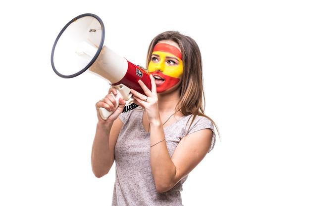 Frau anhänger treuer fan der spanischen nationalmannschaft gemalt flagge gesicht bekommen glücklichen sieg schreien in megaphon mit spitzen hand. fans emotionen.