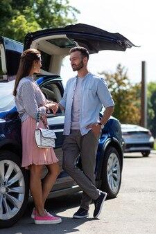 Frau anschauen. bärtiger mann, der seine schöne stilvolle frau anschaut, während er in der nähe des autos steht