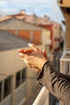 Frau applaudiert in einem balkon von spanien gruß für arbeiten von ärzten, krankenschwestern, richtlinien