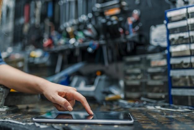 Frau arbeiten in der werkstatt surfen im internet