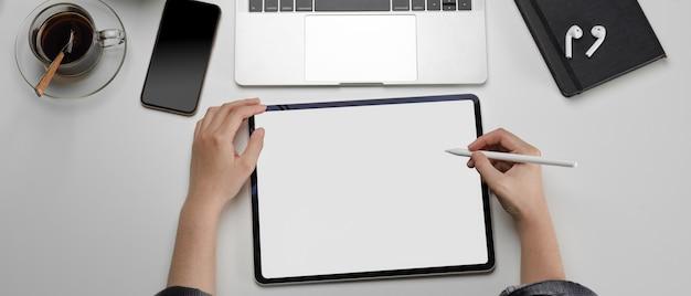 Frau arbeitet am arbeitsbereich mit mock-up-tablet, smartphone und anderen verbrauchsmaterialien