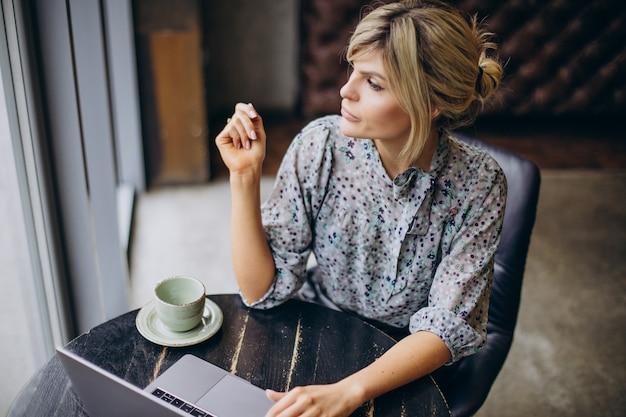Frau arbeitet am computer und trinkt kaffee Kostenlose Fotos