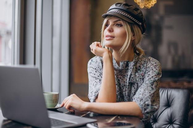 Frau arbeitet am computer und trinkt kaffee