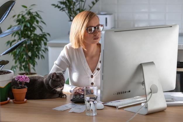 Frau arbeitet am computer vom heimbüro während der selbstisolationsperiode, katze schläft in der nähe auf dem tisch