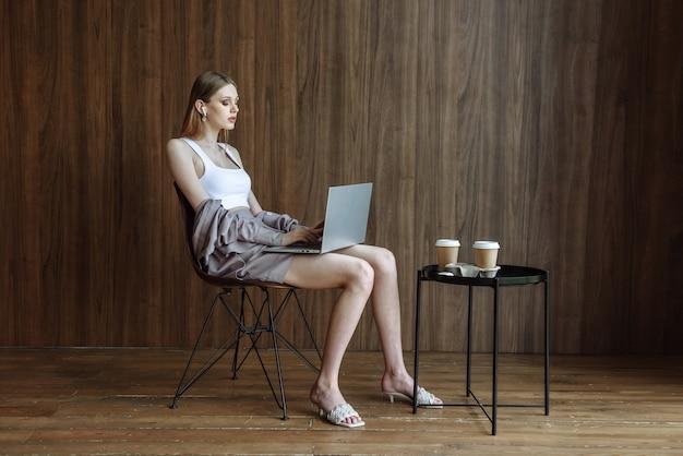 Frau arbeitet am laptop, während sie auf einem stuhl sitzt
