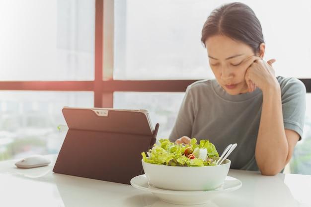 Frau arbeitet an ihrem laptop mit einer schüssel gemüsesalat im büro