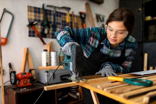 Frau arbeitet in der werkstatt mit bohrhammer