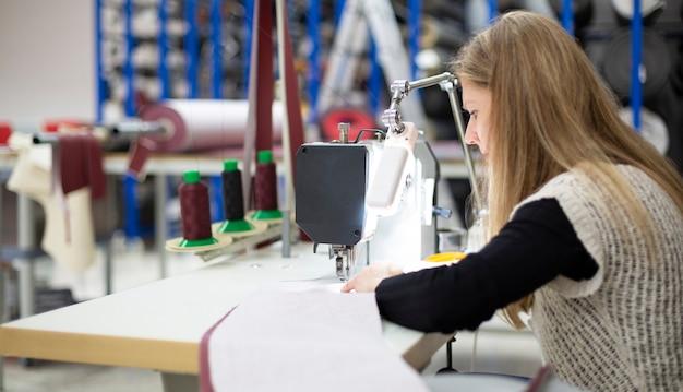 Frau arbeitet konzentriert mit einer industrienähmaschine
