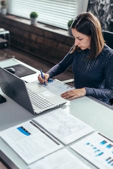 Frau arbeitet mit dokumenten, die am tisch sitzen.