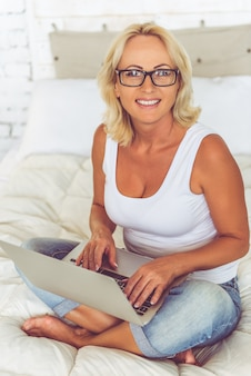 Frau arbeitet mit einem laptop auf ihrem bett zu hause