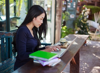 Frau arbeitet mit Laptop im Café