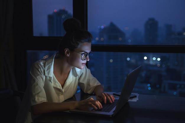 Frau arbeitet mit laptop zu hause während der nacht.