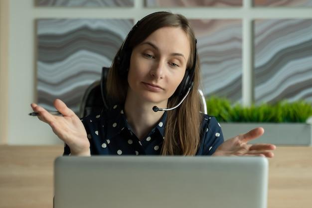 Frau arbeitet online mit headset und laptop im büro