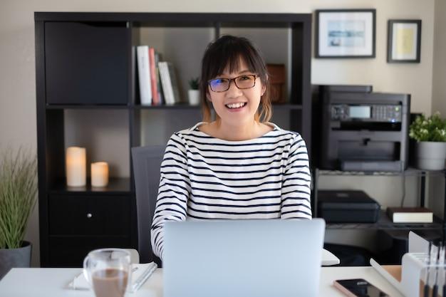 Frau arbeitet zu hause büro. lächeln und in die kamera schauen.