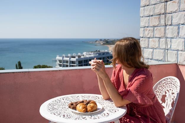 Frau auf balkon mit wunderschönem meerblick