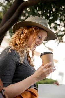 Frau auf bank, die kaffee trinkt