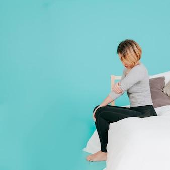 Frau auf bett mit verletzendem ellbogen