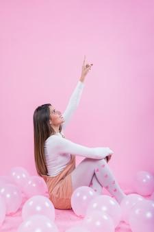 Frau auf boden mit ballonen finger oben zeigend