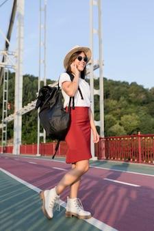 Frau auf brücke mit sonnenbrille und hut unter verwendung ihrer ohrhörer