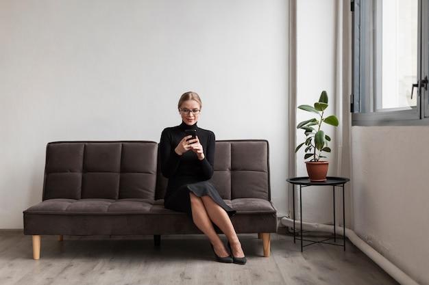 Frau auf couch unter verwendung des mobiles