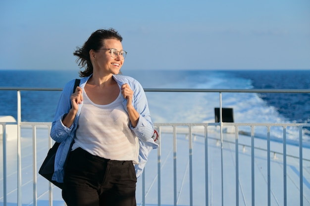 Frau auf deck der fähre, frau, die in starkem wind steht, seereise genießt, sonnenuntergang am meer, kopienraum