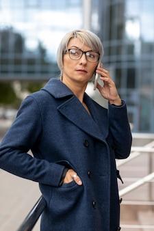 Frau auf dem balkon, der über telefon spricht