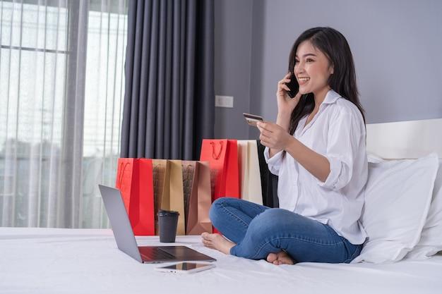 Frau auf dem bett, das online mit smartphone und kreditkarte kauft