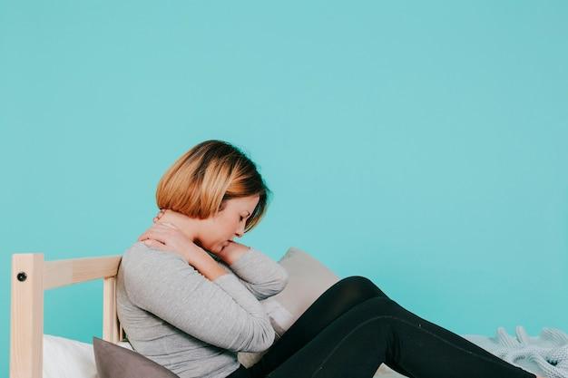 Frau auf dem bett mit nackenschmerzen