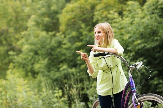 Frau auf dem fahrrad, das weg mit kopienraum schaut
