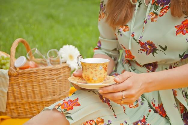 Frau auf dem picknick sitzt auf der gelben abdeckung und hält tasse tee oder kaffee.