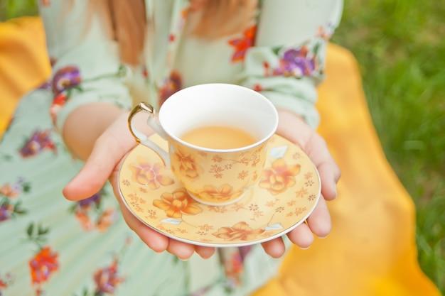 Frau auf dem picknick sitzt auf der gelben abdeckung und hält tasse tee.