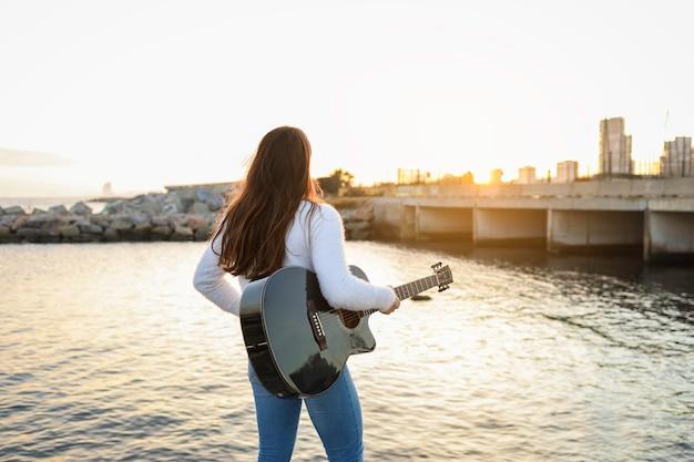 Frau auf dem rücken hält die gitarre