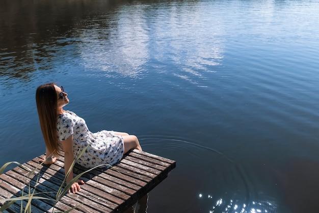 Frau auf dem see. junge frau, die weißes kleid trägt, genießt natur und ruht sich auf einem hölzernen pier auf dem see aus
