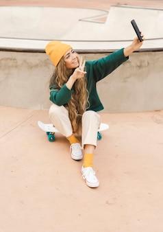 Frau auf dem skateboard, das selfie nimmt