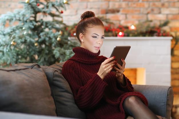 Frau auf dem sofa mit einer tablette