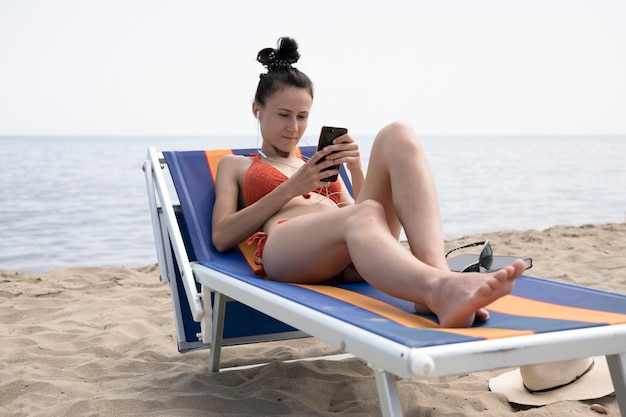 Frau auf dem strandstuhl, der telefon betrachtet