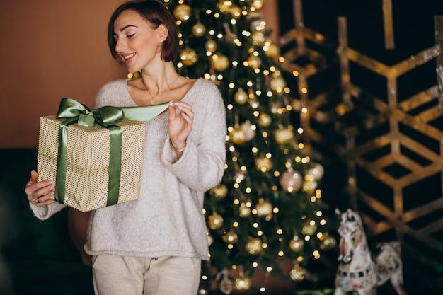 Frau auf dem weihnachten, das ein weihnachtsgeschenk durch den weihnachtsbaum hält