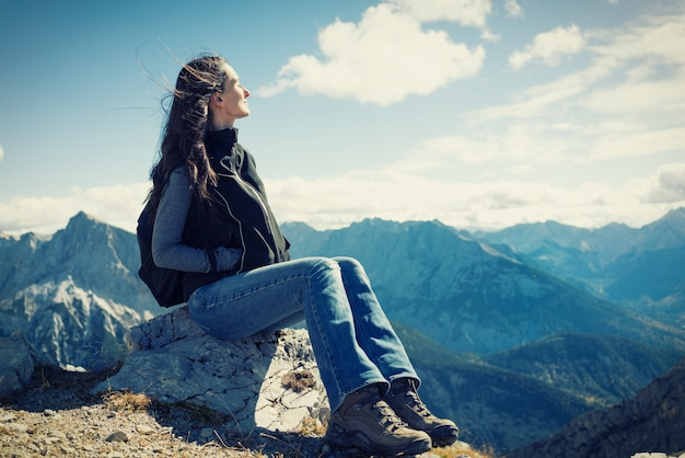 Frau auf der bergwanderung, die den rest hat, der auf felsen sitzt