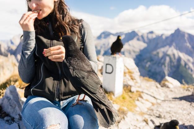 Frau auf der bergwanderung, die stillsteht, brot essend