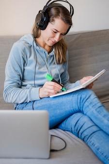 Frau auf der couch, die an der online-klasse teilnimmt und sich notizen macht