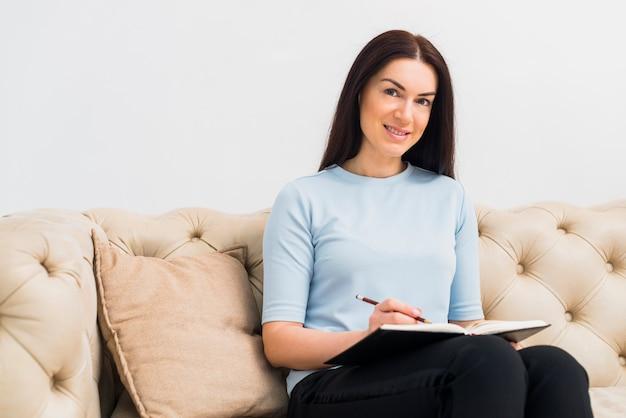 Frau auf der couch, die etwas in notizbuch schreibt