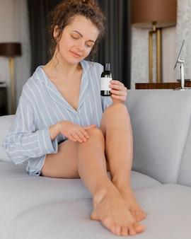 Frau auf der couch, die lotion auf körper anwendet