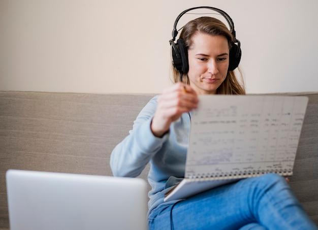 Frau auf der couch, die notizen von der online-klasse macht